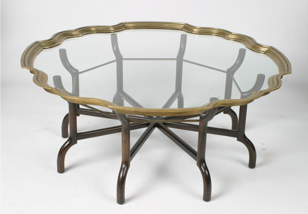 Dark mahogany sculptural base table with brass stretchers, heavy thick brass framed glass top