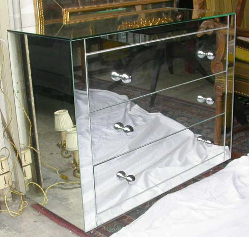 A small three drawer commode, base and façades all mirrored with chrome metal ball handles, interior has been painted in off white.