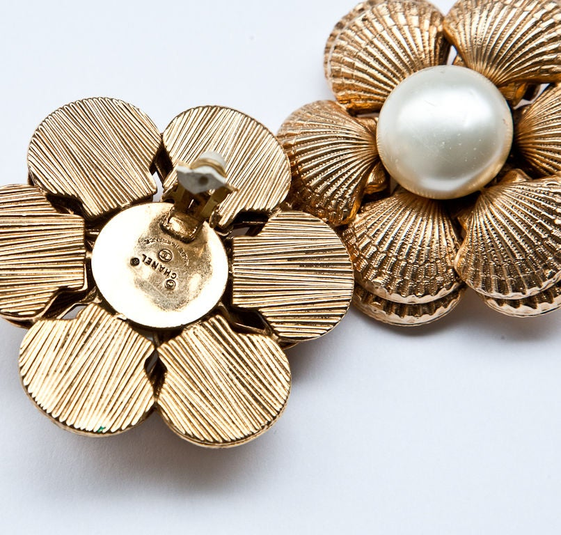 Large Round gold clip on earrings with clusters of clam shell motifs and a rounded centered pearl.