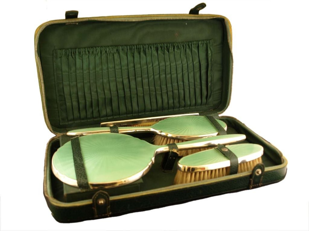 Sterling silver and enamel dresser set in original green zippered case.  Includes hand brush, handled brush, comb & handled mirror. All enamel, silver & comb in excellent condition. (enamel color is a rich mint green) Hallmarks indicate Brimingham