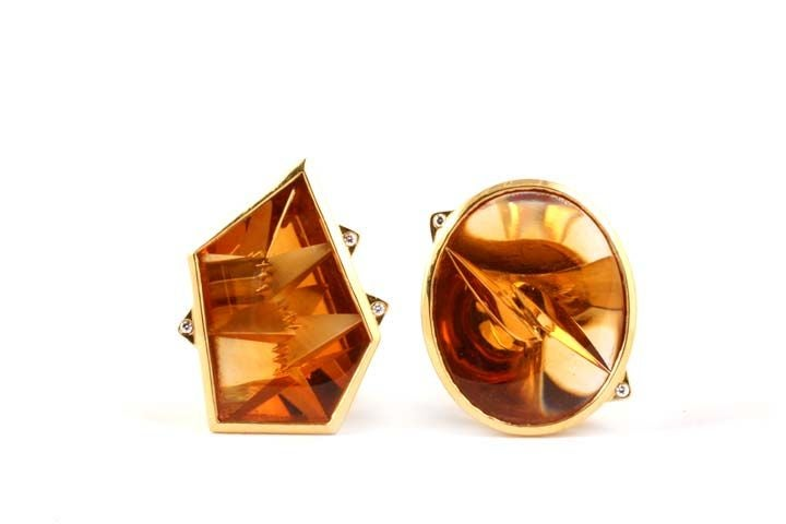 the above image shows gold earrings with intricately cut Citrine gems