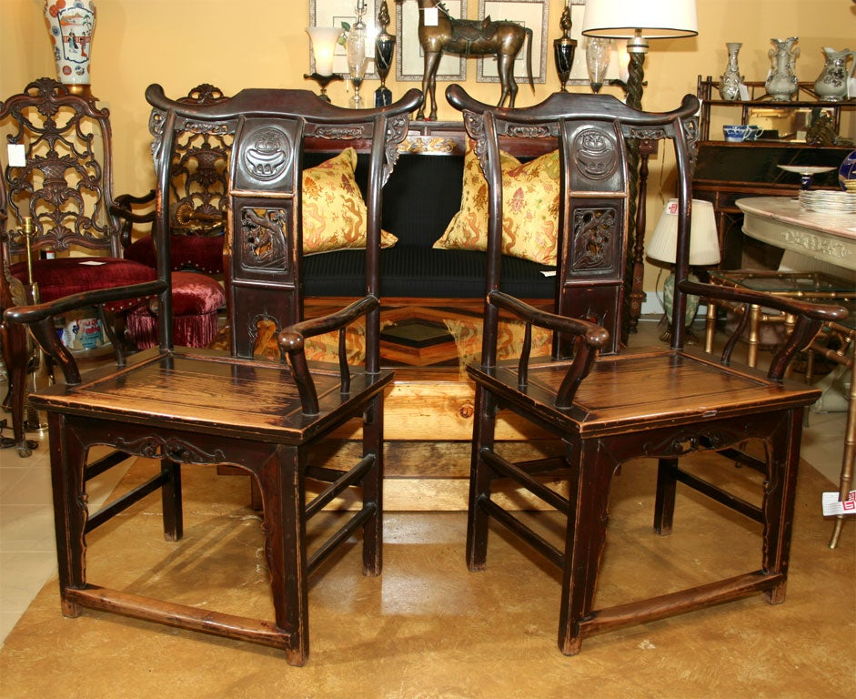 A pair of Chinese elm armchairs with shaped crest rail and curved back splats with pierced and carved cartouches.