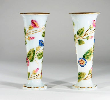 Lovely and rare pair of 19th century Baccarat Opaline glass vases. Each has raised molded floral and vine decoration that is painted with vibrant enamels. The petal foot and rim is gilded to accent this pair- perfect for a mantle or any other