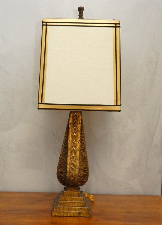 This arts and crafts table lamp is probably English and from the earlier part of the last century. The lamp sits on a five tiered base with a shaped central element raising to hold the upright light fitting. The whole is covered with embossed brass.