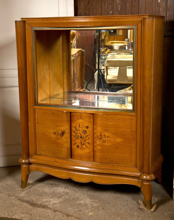 Bronze mounted satinwood marquetry cabinet in the style of Jules Leleu. Two lower doors and one-drawer. Mirrored upper section accommodates glass shelves.