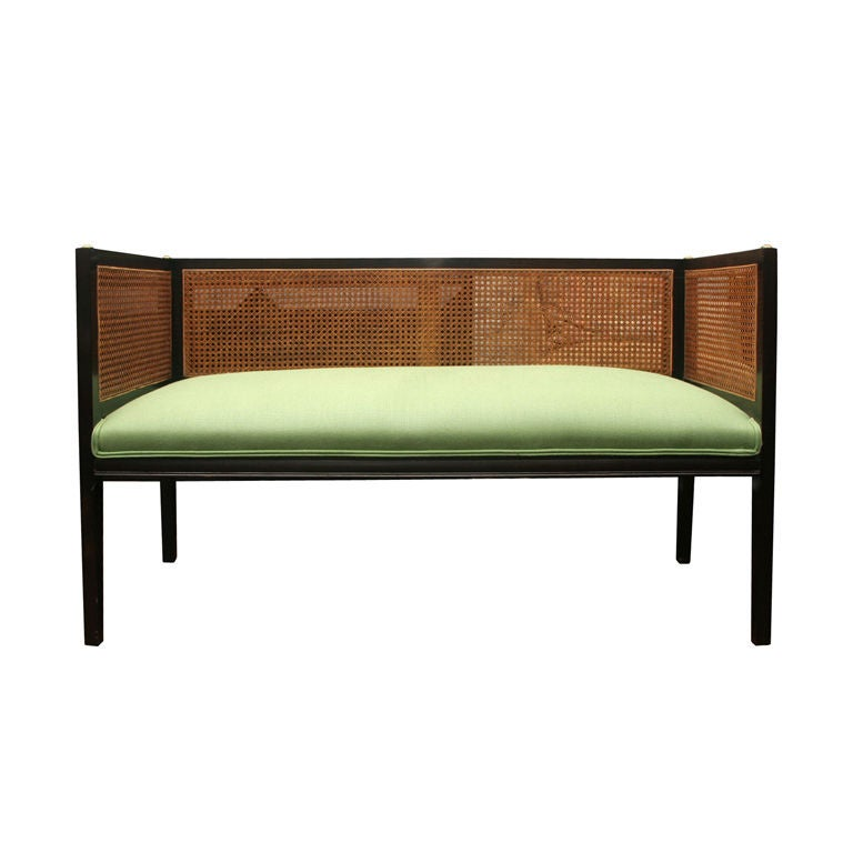 dark mahogany caned bench upholstered in green linen at