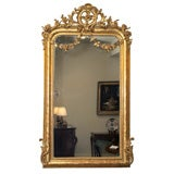 Antique French giltwood mirror w/floral swags and crest.