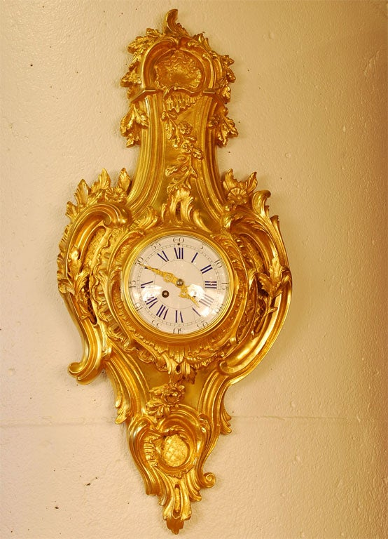 Louis XV style Cartel clock in gilt bronze with painted porcelain dial. The case has been re-gilded, and features typical rocaille ornament such as laurel leaves and berries, flowers and shell forms. The clock runs and strikes on the hour and