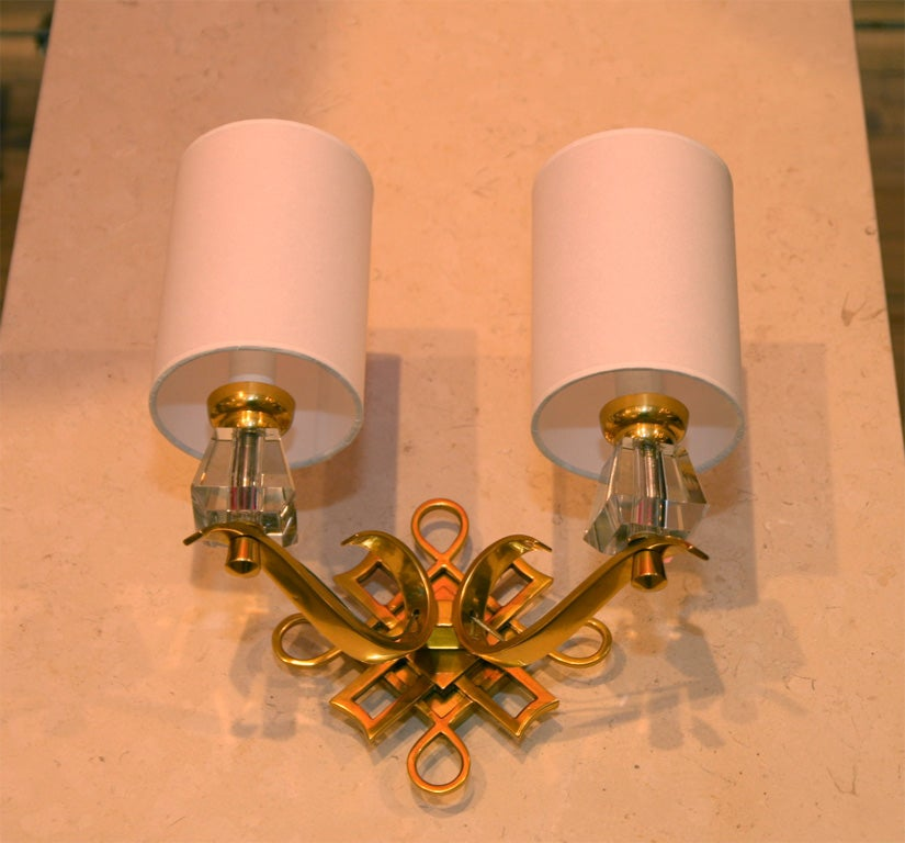 Elegant pair of sconces. Cast bronze and crystal. Two pairs are available.