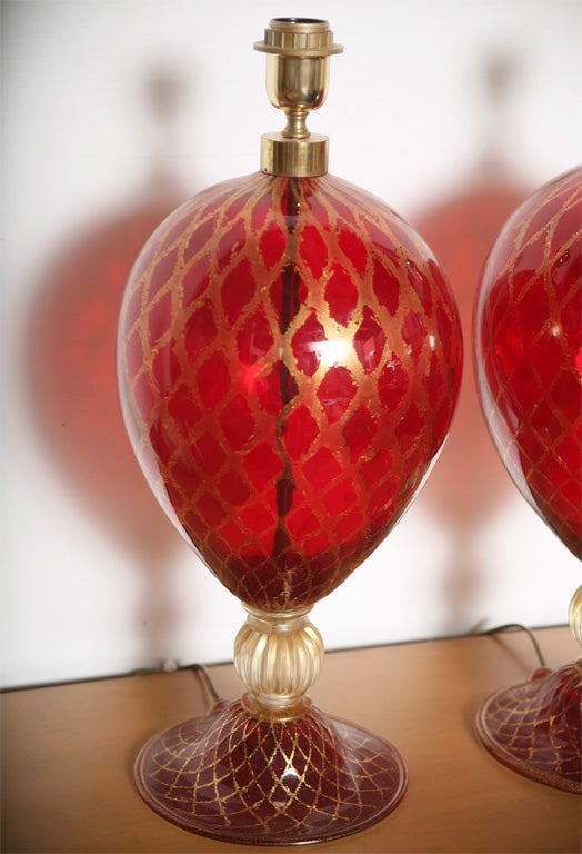Those ruby red Murano glass lamps with the accent of gold leaf painted as Venetian style will bring to your interior a very rich feeling of abundance and glamour. As you can see on the picture, one lamp is a little larger in weight and height than