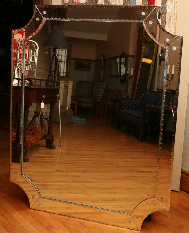 This very dramatic large modern mirror has circle cut corners and excellent but restained engraving to the mirror border frame. The engraving is in the form of an elongated oval with a small diamond separating each oval. All the edges are beveled