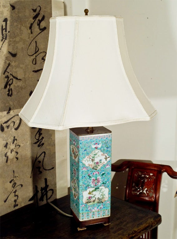 A table lamp, converted in the 30's from a 19th Century porcelain vessel, delicately painted in famille rose over a turquoise background and seated on a custom rosewood stand. New Shade.