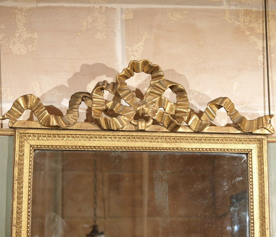 """French Louis XVI period painted and gilded mirror with """"ruban de Sevigne"""" decoration at top, circa 1780."""