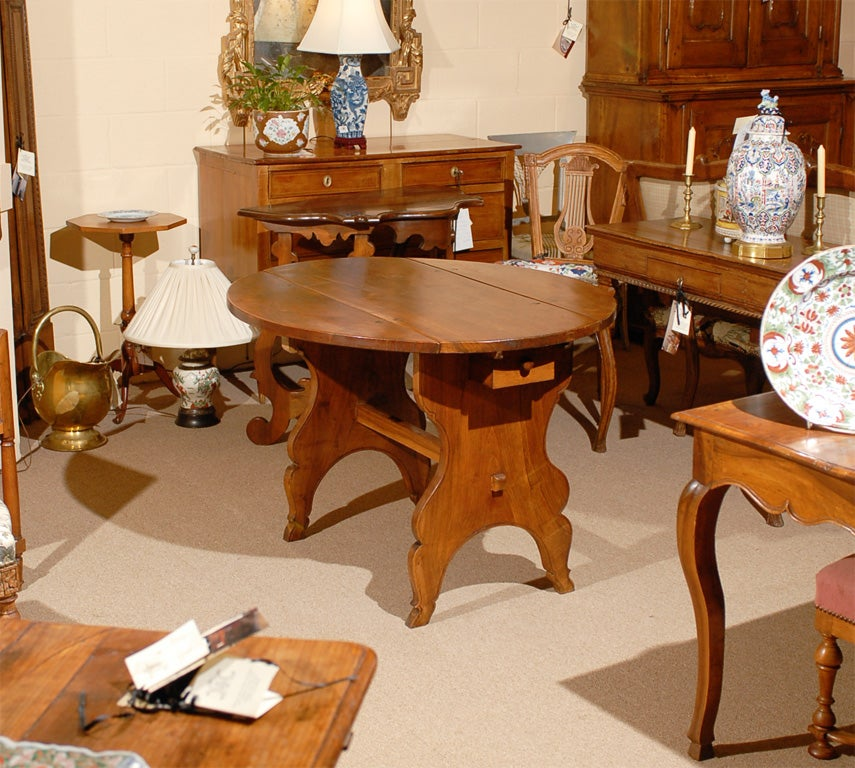 An oval drop leaf table in rich walnut with two drawers and stretcher. The table dating 18th century and Swiss in origin.   For many more fine antiques please visit our online galleries at William Word Fine Antiques: Atlanta's source for antique