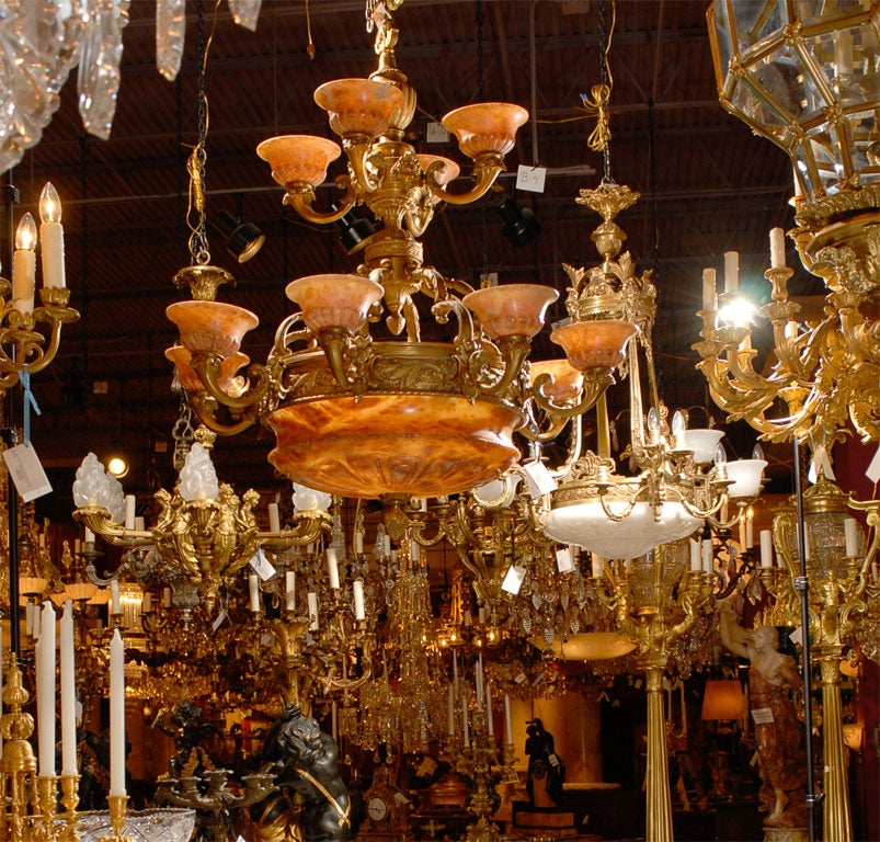 Magnificent twelve-arm two-tiered gilt bronze chandelier with alabaster dome and shades, dome has four inside lights.