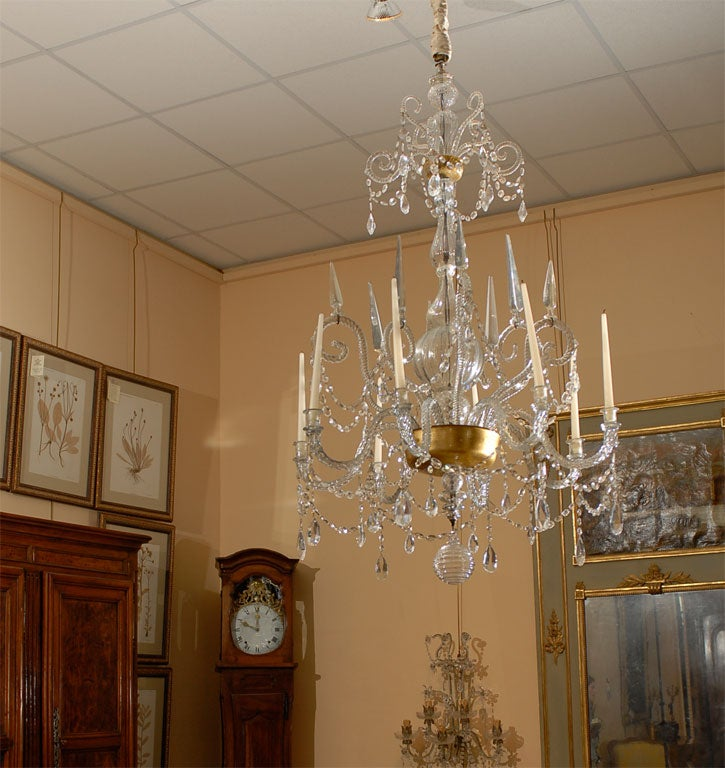 A Fine and Impressive Venetian Crystal Chandelier with solid crystal arms and 8 lights, originating in Italy during the 18th Century.    The circular corona with stylized twisted crystal scrolls, above a baluster shaped stem affixed with reverse