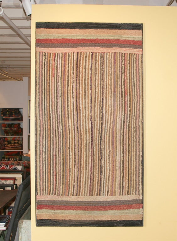 Linear geometric hooked rug. A precursor of modern paintings, this geometric incorporates rich yet subtle earth tones. Mounted on a stretcher for wall hanging.