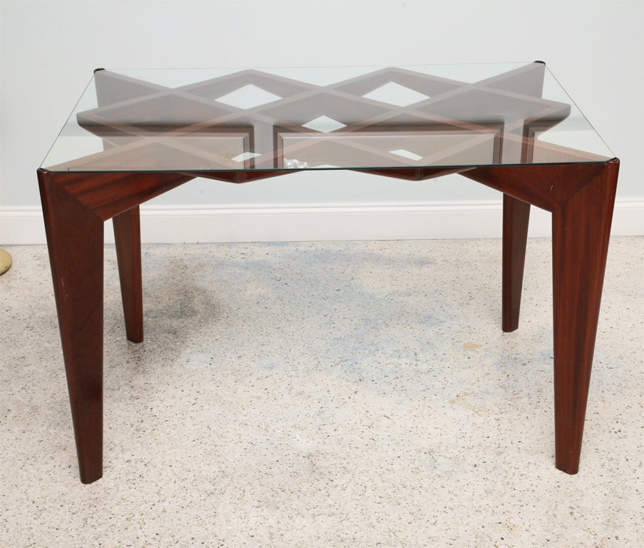 The inset rectangular glass above a pierced geometric top and angled cross members on tapering legs.  This table closely relates to a documented circular low table in Gio Ponti, Ugo de la Pietra, and is identical to a low table in the archives of