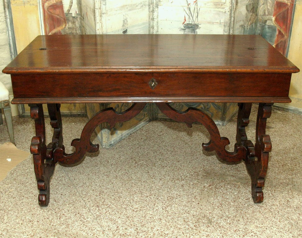 A 19th century Italian writing table, the top folds back and the front drops to reveal drawers and a writing surface. The table is mounted on carved, cartouche shaped legs with a curved, carved stretcher.