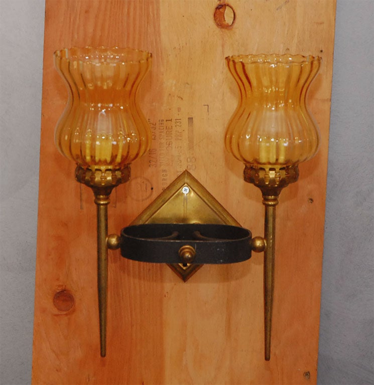 Diamond shaped brass backing with oval iron band design holding two lights. Topaz colored glass shades give these circa 1950's sconces a nice warm look.