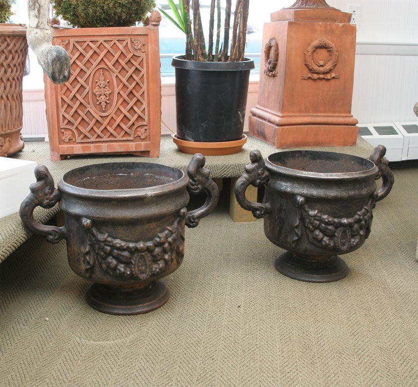 Black cast iron urns with beautiful mermaid handles and garland decor on the body.