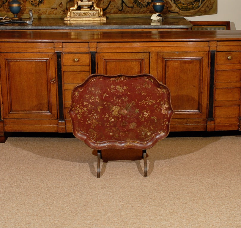 A Tray on folding stand with shaped oval form, painted burgundy and gilt chinoiserie design and ebony base.   William Word Fine Antiques: Atlanta's source for antique interiors since 1956.