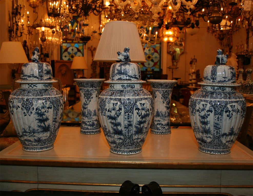 A set of five Dutch delft vases comprised of three ginger jar-shaped ribbed covered vases with lion finial. The fine decoration depicting figures in landscape and seashore settings in blue on a white ground.