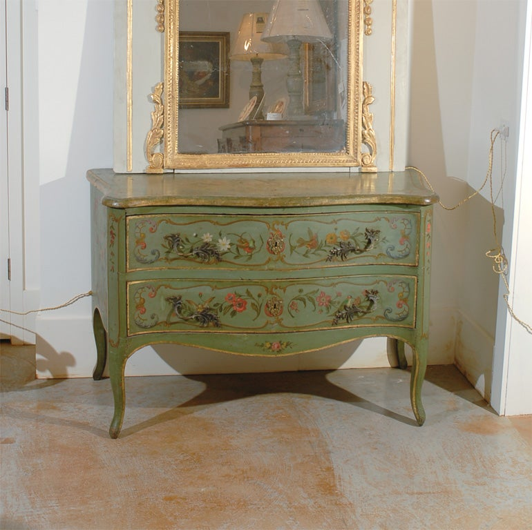 An Italian Rococo style green painted two-drawer commode from the 19th century. This exquisite Italian chest of drawers is painted in a soft green color with gilded highlights. Delicate painted cartouches on the drawers surround floral motifs with