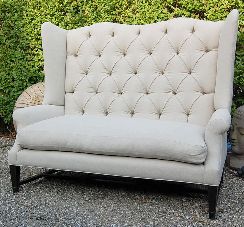 Monumental wing back sofa with and down seat on a stylized dark wood base with either a tufted or tight back... in natural linen or COM.
