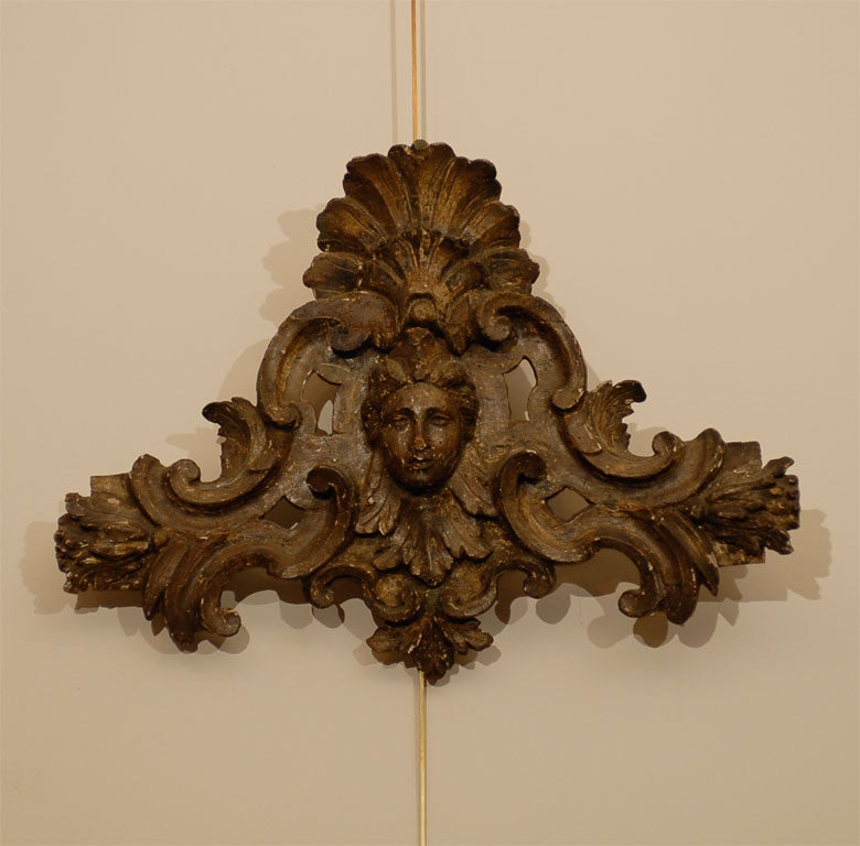 A Pair of Italian Silvered Wood Wall Carvings originating during the second half of the 18th century.<br /> <br /> Each carving centered by a female mask flanked by pierced C scroll designs and surmounted by a shell crest.<br /> <br />