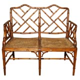 Antique English faux bamboo settee. Caned seat.