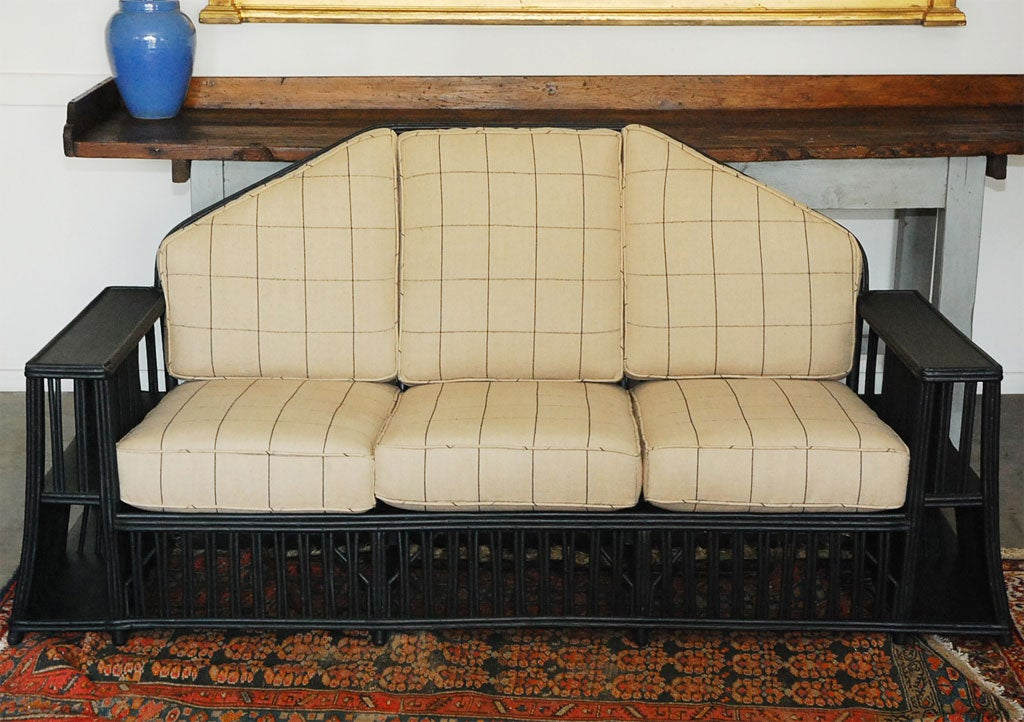 A larger American wicker settee, from the first half of the last century, having newly upholstered cushions.It has bookcases set into the arms facing in and out.  The arms are nice and wide. Useful and ready to make a good impression in your next