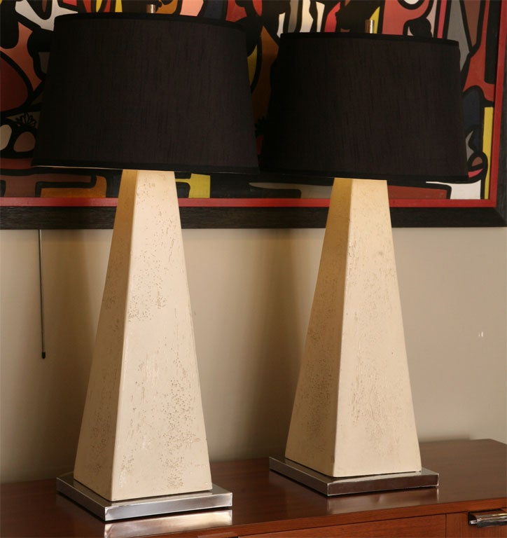 Stunning scale and beauty with these architectural gems. Tall obelisk forms of textured gesso and plaster over wood atop nickel silver plinth bases. The smooth textured surface is like unfilled travertine or cut coral rock. Sleek, urbane and