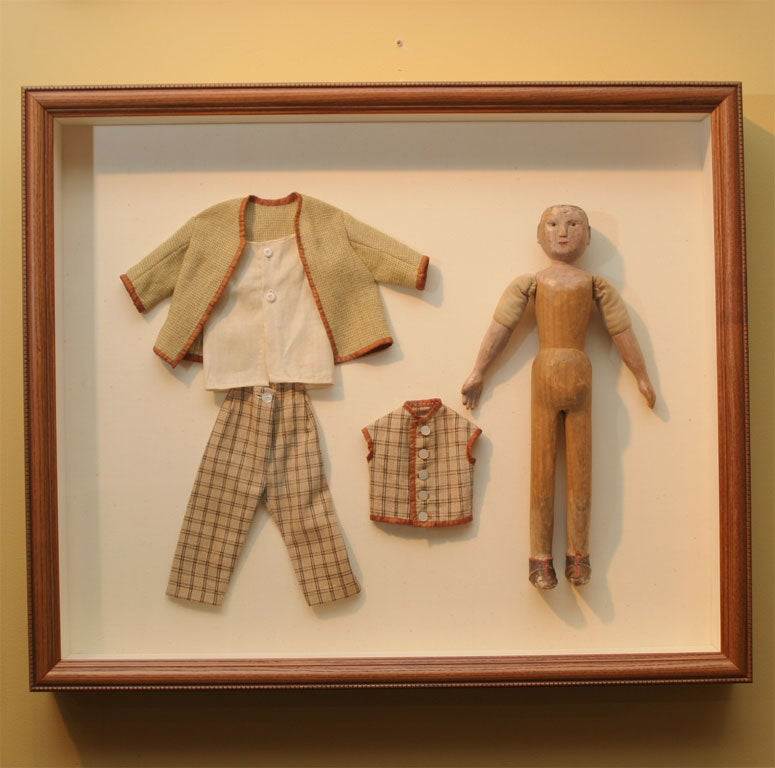 Folky carved wooden boy doll with original painted surface and leather shoes. Clothes original to doll. Archivally framed behind ultraviolent plexiglass in wood shadowbox with beaded edge.