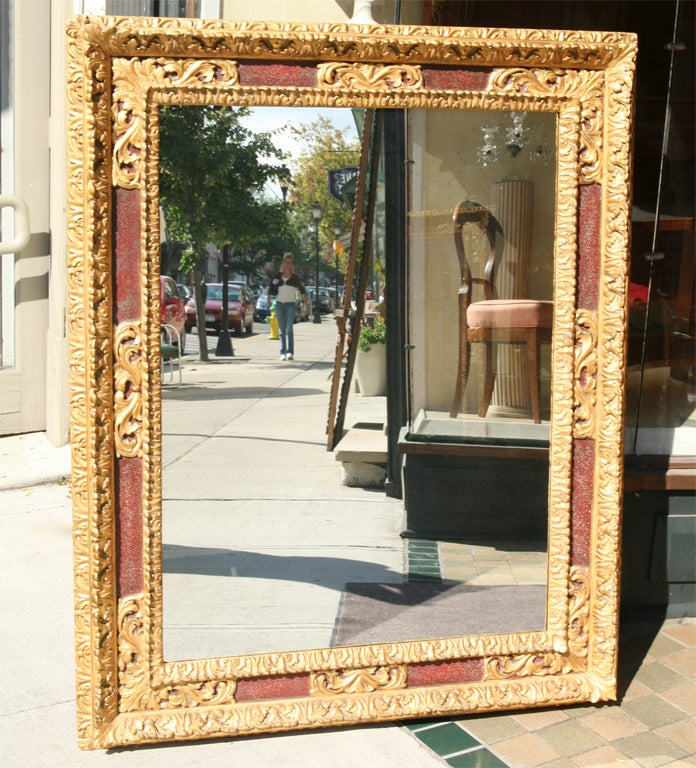 This extravagant frame in carved wood and plaster from Italy has as its surface treatment raised gold leaf decorative corners and central cartouches with the lower sections in a painted faux porphyry. The entire mirror frame has then been antiqued