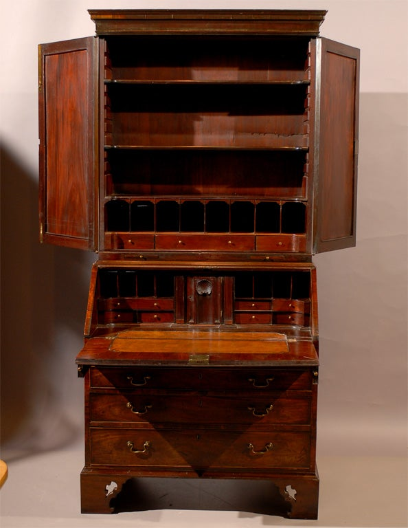 An 18th century early George III mahogany bureau bookcase with blind paneled doors and bracket feet, originating in England during the mid 18th century.