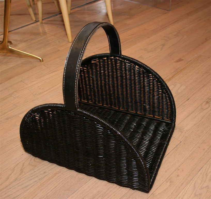 Wicker basket with a leather covered handle, it's ample size makes it suitable for either log or magazine storage.