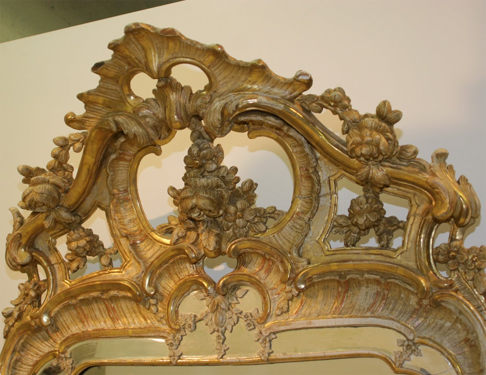 A Swedish Rococo gitwood mirror, Third Quarter 18th Century, the divided mirror plate surrounded by a molded giltwood frame with a beveled glass panel, surmounted with a pierced shell, foliate and scrolled crest, the lower section with similar