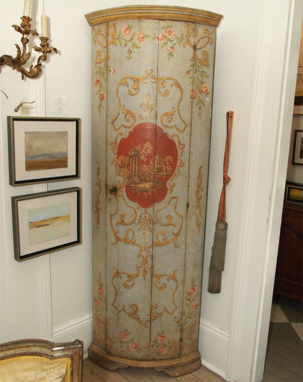 Corner cabinet painted French blue with gold decorative scrolls and pink roses. Center pasture scene painted in deep red and shades of gold.