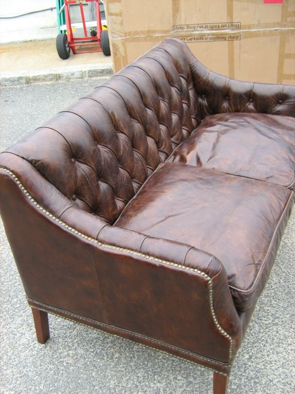 Antiqued Leather Two Seat Sofa With Tufted Back And Tufted Inside Arms