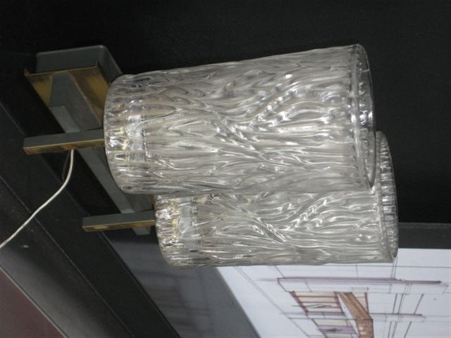 A pair of sconces with sculpted and textured glass shades. Iron and brass designed base.