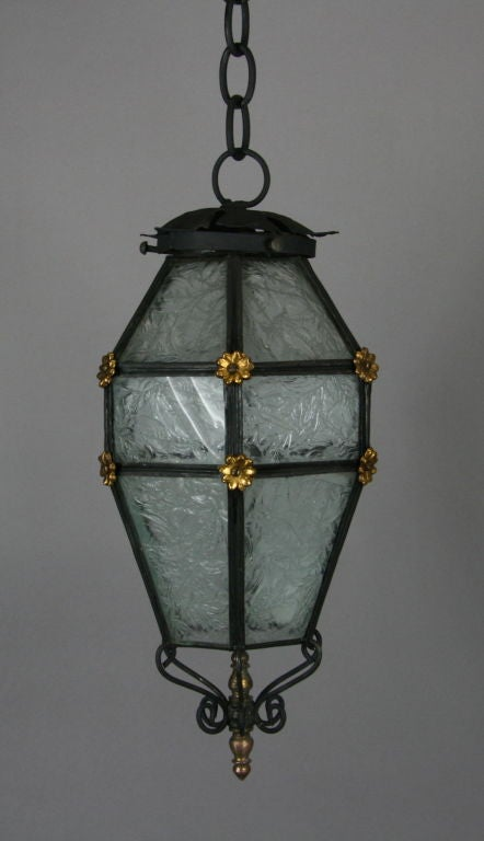 A blackened multi-sided patterned glass set in a finely iron frame embellished wit gilt rosettes.Lantern  14 inches H for 6.5 inches W,One edison -base 75 watt bulb List $ 1275  net $775 no additional discounts