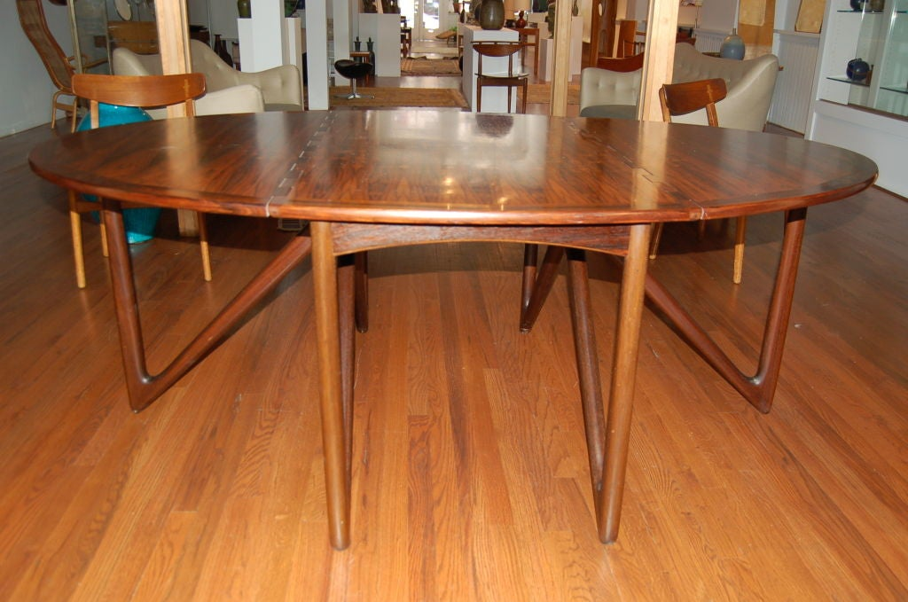 Exquisite oval drop-leaf dining table designed by Kurt Östervig for Jason Möbler, Denmark, 1950s. Dramatic V-shaped mahogany gatelegs and bookmatched rosewood top with solid rosewood edging.