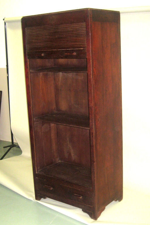 A rare French Art Deco Colonial roll top / armoire / cupboard / storage / linen press / bookcase with three internal shelves and one lower storage drawer. The piece shows the influences of sober modern and French Art Deco movements and is