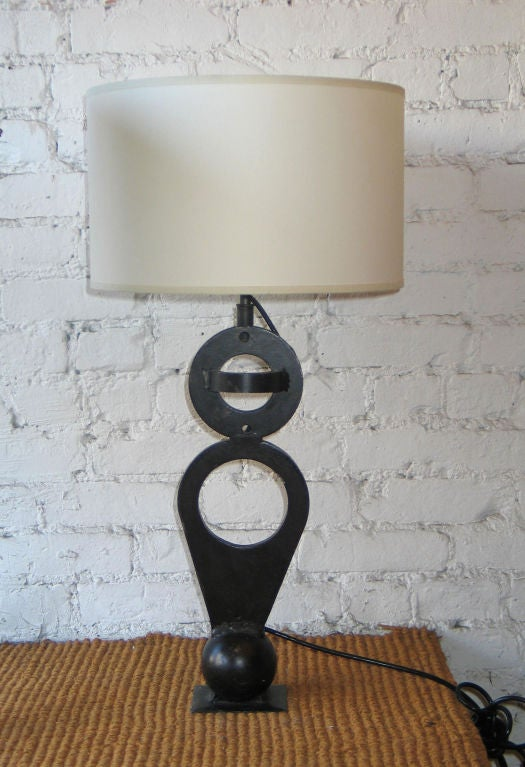 Pair of French Mid-Century Moderntable lamps in handwrought iron in the form of modern geometric sculptures utilizing the forms of a ball and circles.  Initialled with artists initials on rear.