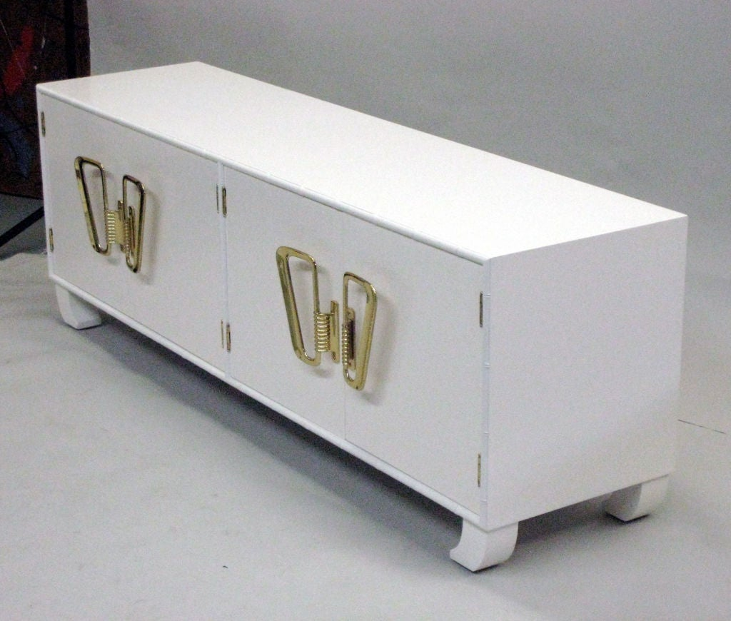 Italian Mid-Century Modern white lacquered cabinet, sideboard, chest, commode, credenza, etagere or shelves with exotic inward turned legs and faux bamboo frame. Stunning solid brass door hardware completes the dramatic appearance.