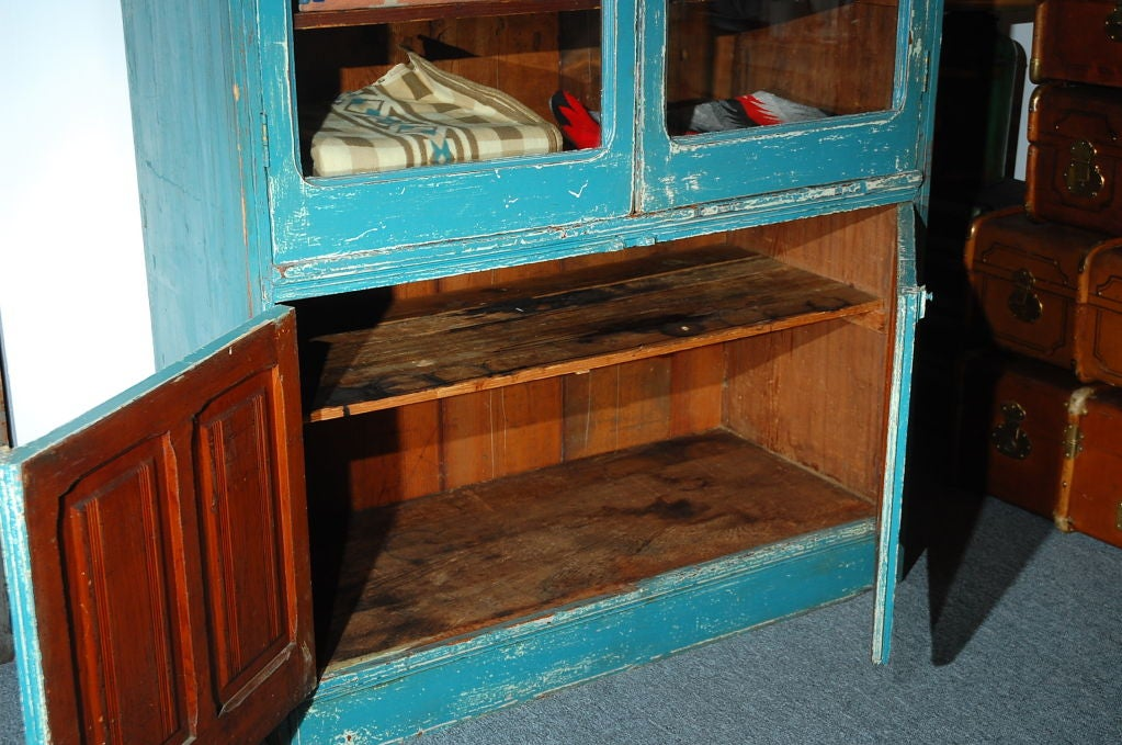 LATE 19THC AND RARE ORIGINAL BLUE PAINTED STEP BACK CUPBOARD IN AS FOUND CONDITION WONDERFUL .SQUARE NAILS CONSTRUCTION ALL ORIGINAL HARDWARE AND HINGES WITH PANNEL DOORS AND GLASS THE INSIDE OF THE CUPBOARD HAS A WONDERFUL OLD AGE PATINA TOO.