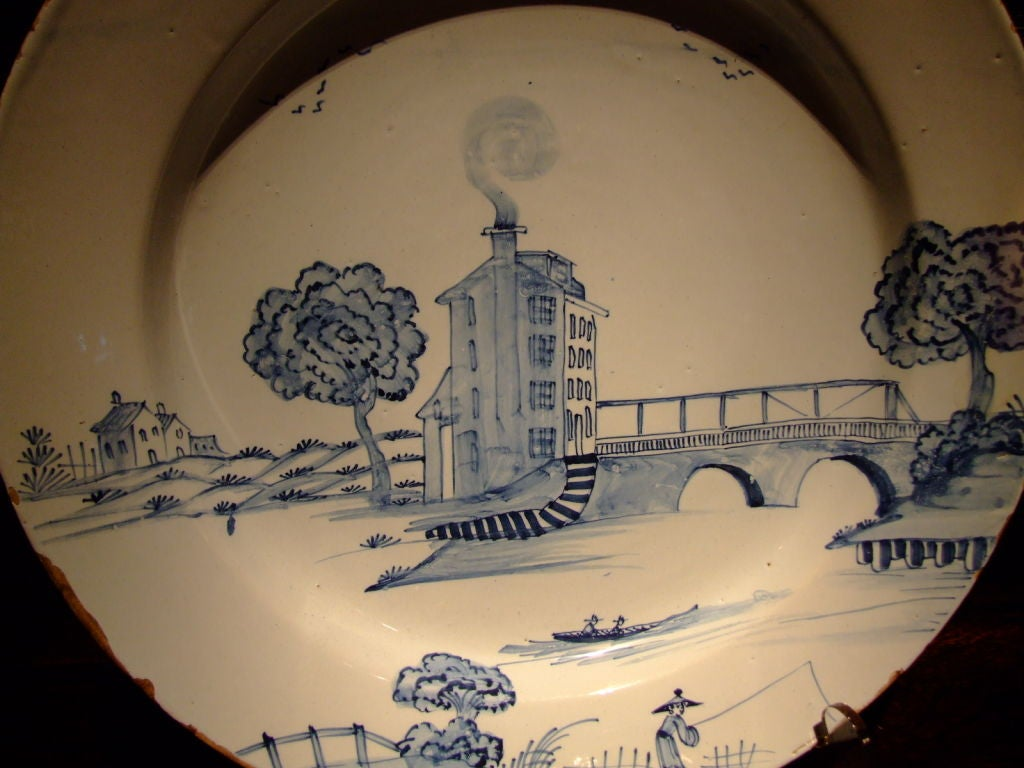 18th century English Delft charger having a blue-gray glaze probably from London depicting a rare subject matter which is asymetrical showing a tower house next to a bridge.  The artist painted with a fine, delicate hand probably by a master