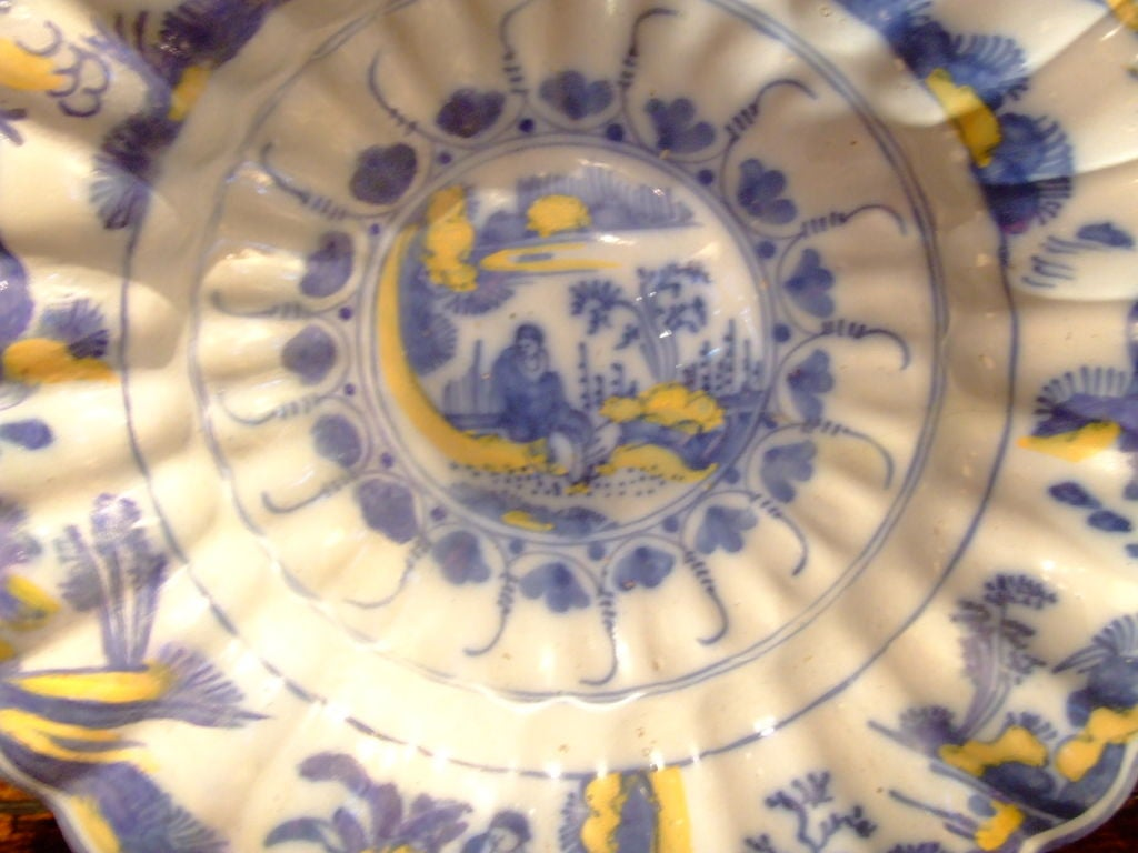 An early and rare 18th century Dutch Delft sweetmeat dish having eggyolk and soft gray-blue overall decorative design with a depiction of a lady sitting in her ornamental garden, and an attractive three-dimensional lobed form.