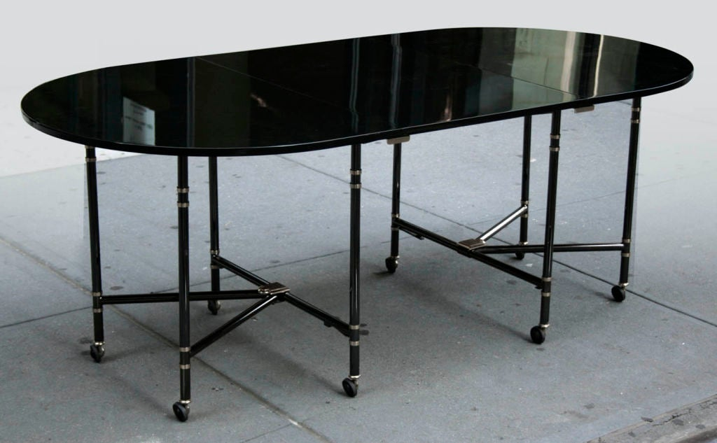 Royal Dining Table by Maison Jansen<br /> France, c. 1972<br /> A spectacular Royal extension table by Maison Jansen. Dark grey lacquer surface on blackened steel legs mounted with gold plated accents. Versatile table extends from 55 inches to